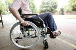 A disabled man propelling his wheelchair.